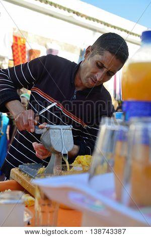 ESSAOUIRA - JULY 14: Unidentified man sells fresh orange juice in market of Essaouira, Morocco, July 14, 2013. Essaouira is one of the most popular tourist place on Atlantic coast in Morocco.