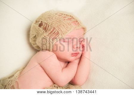 A newborn is asleep. Hands under cheek