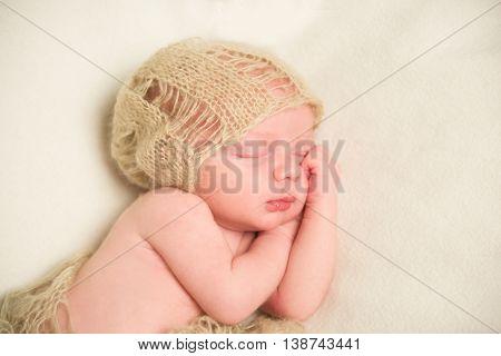 A newborn is asleep. Hands under cheek