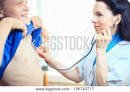 Doctor listening to the heartbeat of her patient with a stethoscope