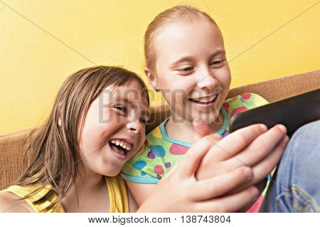 Two little girls using a home mobile phone.