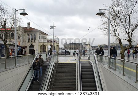 Istanbul Turkey - March 16 2013: Old Kadıköy Pier. New Kadikoy-Kartal subway exit Kadikoy. On a cold winter day moving subway and ferry stop people.