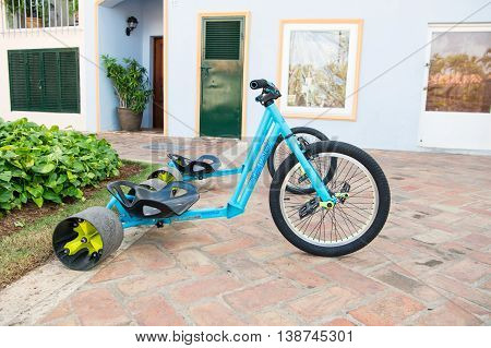 La romana Dominican Republic - February 16 2016: cool sport bicycle or tricycle blue color with iron and plastic hull and big rubber tire for sand has three wheels standing on stony road outdoor with nobody near building