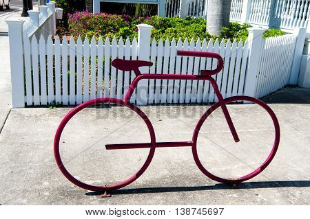 statue of iron bicycle pink color encourages citizens to ride bicycles sunny day outdoor near wooden white fence