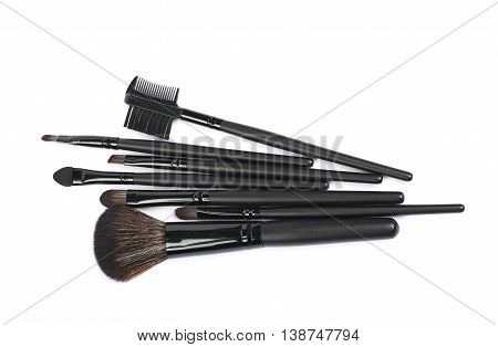 Pile of multiple black makeup tools and brushed isolated over the white background