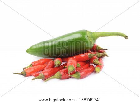 Pile of red italian peppers with a green jalapeno over it, composition isolated over the white background