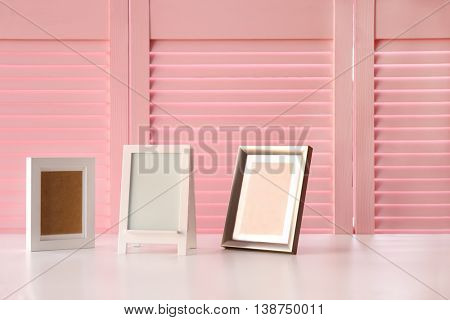 Photo frames on pink folding screen background