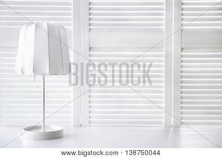 Stylish lamp on white folding screen background