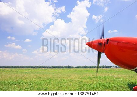 The front part of the aircraft with a propeller against a beautiful sky
