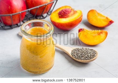 Smoothie with nectarine orange juice chia seeds and honey in glass jar horizontal concrete background