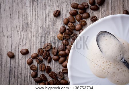 Leftovers of coffee foam on saucer with spoon placed on wooden background with coffee beans. Flat-lay with copy-space.