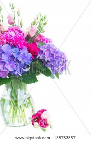 Bright pink peony, eustoma and blue hortensia flowers bouquet in vase close up isolated on white background