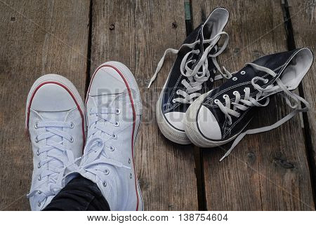 Teenager wearing white shoes sitting next to black snickers on the wooden bridge, choice concept