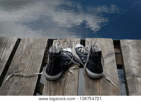 Black teenager's shoes standing on the wooden bridge edge, choice concept