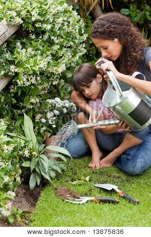 Happy young mother with daughter watering plant