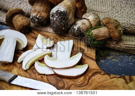 Whole and sliced boletus edulis (king bolete) on a wooden table