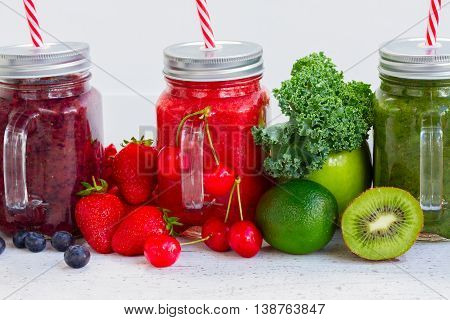Colorful smoothy drinks in jars with igredients close up