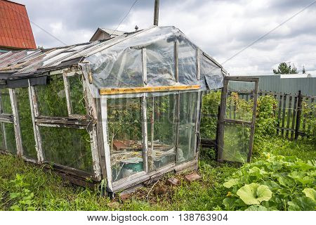 Old greenhouse for growing vegetables made from the material at hand. Russia Siberia