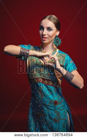 Woman wearing traditional Indian sari with accessories- earrings, bracelets and rings and mehndi henna tattoos gesturing heart shape with hands