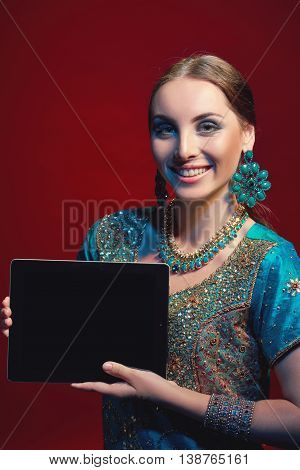 Smiling woman wearing traditional Indian sari with accessories- earrings, bracelets and rings and mehndi henna tattoos showing blank black digital tablet screen