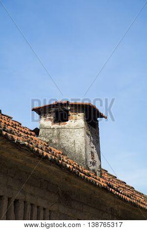 Close up of a brick chimney on tile roof against blue sky