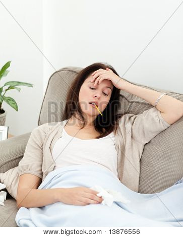 Sick woman taking her temperature with a thermometer on the sofa at home