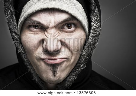 Serious angry man with hooded sweatshirt on dark background