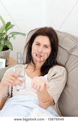 Sick woman showing a pill to the camera lying on the sofa