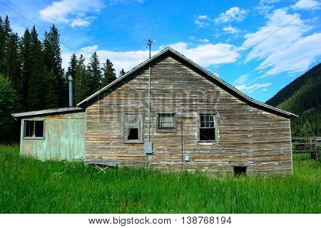 Abandoned Mountain Home With Peeling Paint on a Sunny Day