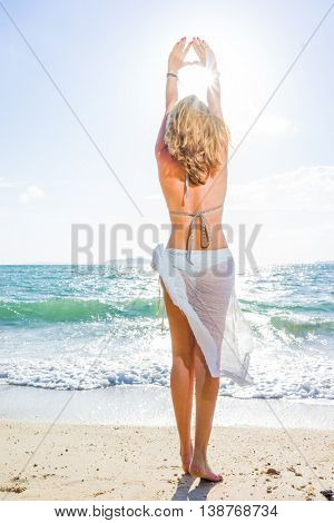 Portrait of young woman wearing a sarong and bikini on the tropical beach