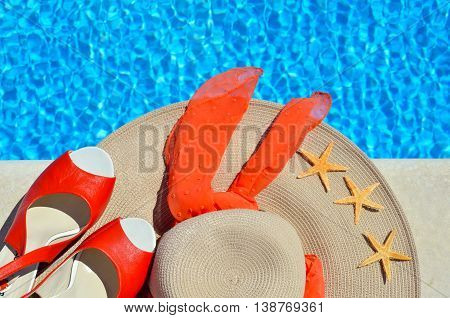 Woman beach hat red sandals and starfish on the pool background.