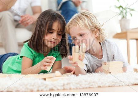 Little boy and girl playing with dominoes together in the living room