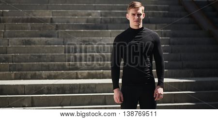 Portrait of a athletic man in a black slinky dress against the backdrop of the stairs