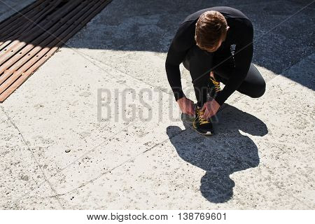 Male athlete tying laces on athletic shoes