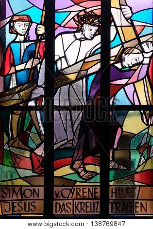 KLEINOSTHEIM, GERMANY - JUNE 08: 5th Stations of the Cross, Simon of Cyrene carries the cross, stained glass window in Saint Lawrence church in Kleinostheim, Germany on June 08, 2015.