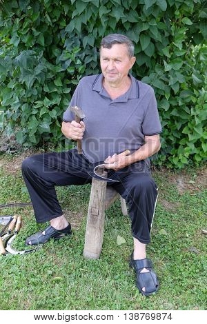 NEDELISCE, CROATIA - JULY 02, 2016: Farmer with hammer and iron tool on the tree stump is sharpening his scythe in Nedelisce, Croatia on July 02, 2016