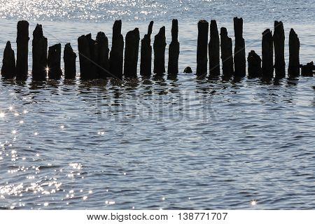 Silhouettes of destroyed breakwaters in the back light on the background of a slightly wavy surface of the Baltic Sea in Kolobrzeg
