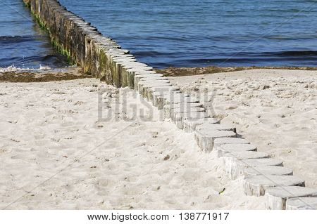 Wooden breakwater built of thick logs driven into deep in the bottom of the sea to protect the beach against the wave action by the Baltic Sea in Kolobrzeg
