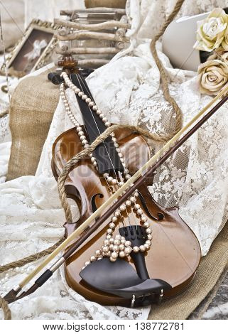 sepia photography of vintage violin with lace pearls and roses - vintage wedding decoration
