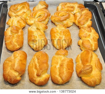 many eclairs cakes closeup on the white paper cooking