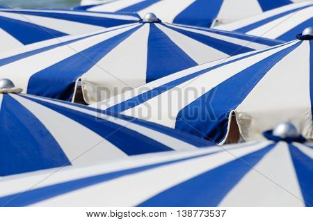 Close up from many blue and white parasols