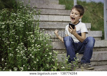 Winning a mobile game. Happy boy looking shocked with opened mouth and eyes on a cell phone. Outdoor. Mobile gaming concept