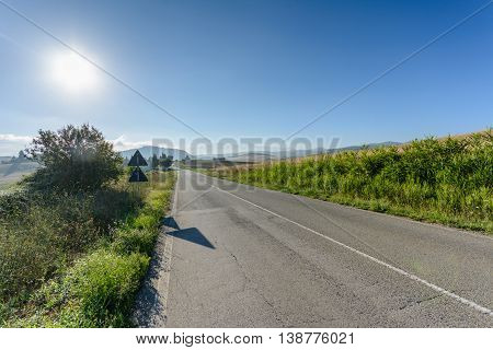 Empty toscana road in the morning with blue sky