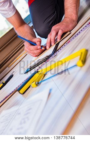 Man laying laminate flooring in construction concept