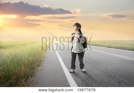 Smiling child with backpack walking on a countryside road