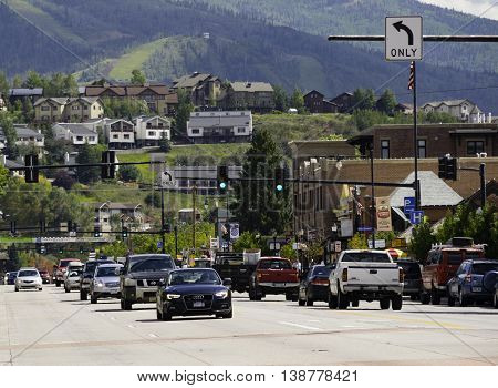 Steamboat Springs CO USA Sept 10 2014 Cars drive on the Main road of the resort town Steamboat Springs Colorado with the Rocky Miuntains in the background