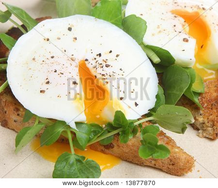 Poached eggs on toast with watercress and pepper.