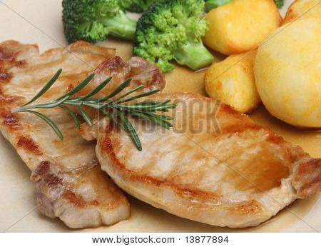 Pork loin steaks with roast potatoes, broccoli and gravy.