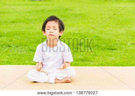 Close up of cute buddhist asian boy sit on wooden mat praying and meditation in the garden.