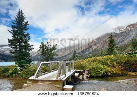 Wood bridge with snow capped mountain and forest in Banff National Park